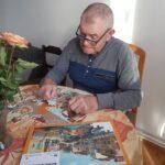 Senior p. Franciszek układając puzzle wypełnia swój wolny czas